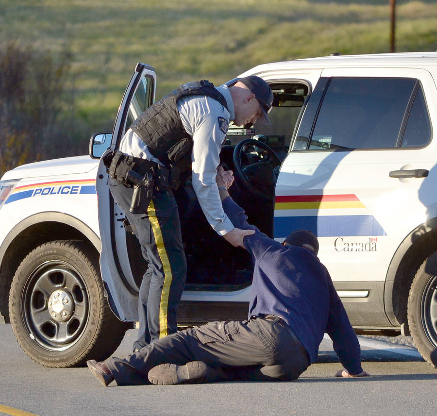 <p>KEITH CORCORAN, PHOTO</p><p>A RCMP officer helps a man to his feet near a police car. Law enforcement took the man into custody for alleged impaired driving.</p>